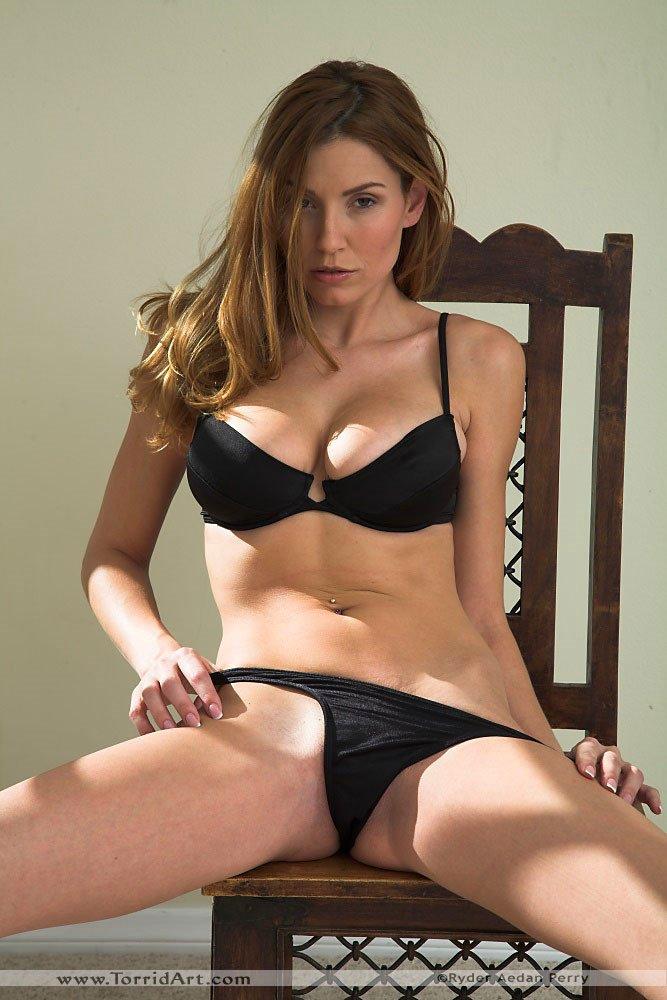 Яркая брюнеточка с большими грудями Jamie Lynn снимает свое черное белье на стуле