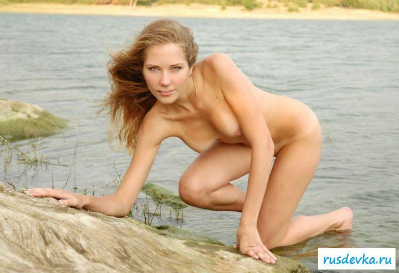 Обнаженная нудистка с стриженной пиздой лежит на солнышке на камнях
