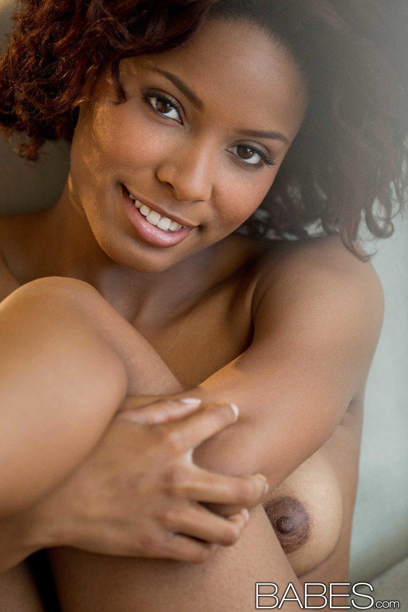 Кудрявая мулаточка с большой улыбкой в голом виде фотографируется на камеру