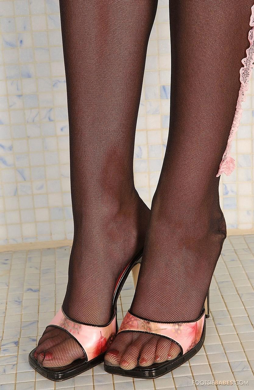 Грациозная блондинка Edina Szegedi показывает свои бритые щелки после того как стягивает туфли и гетры