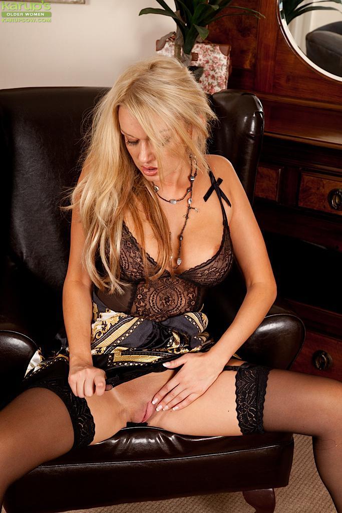 Страстная тетка блондинка в чёрных гольфах Amber Jayne показывает свою идеальную большие титьки и киску