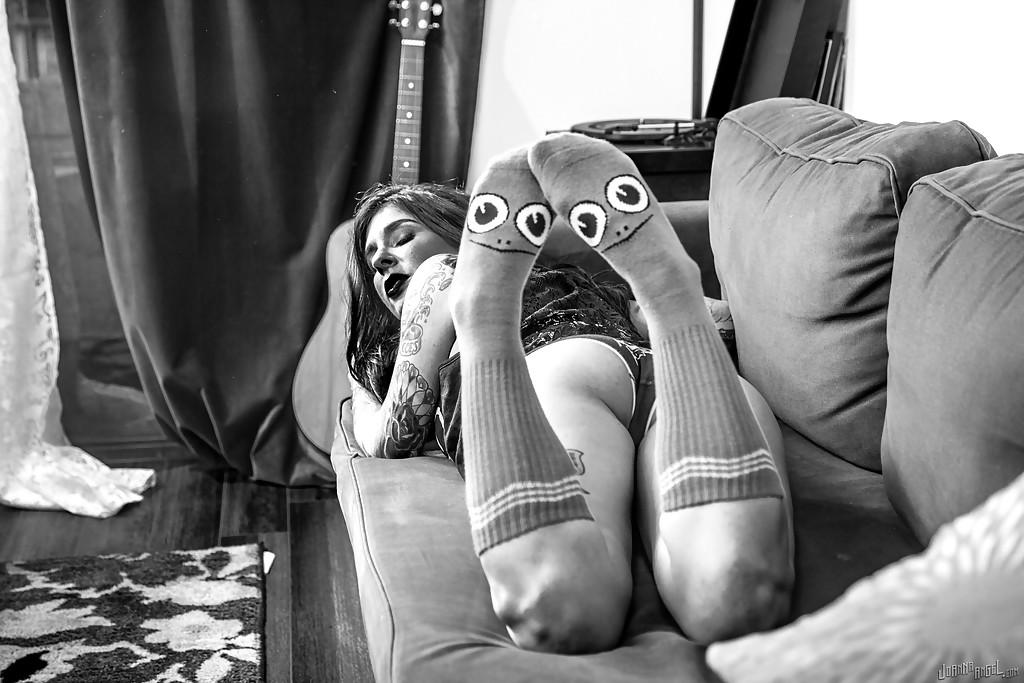Татуированная неформалка в гетрах фотографируется на диване